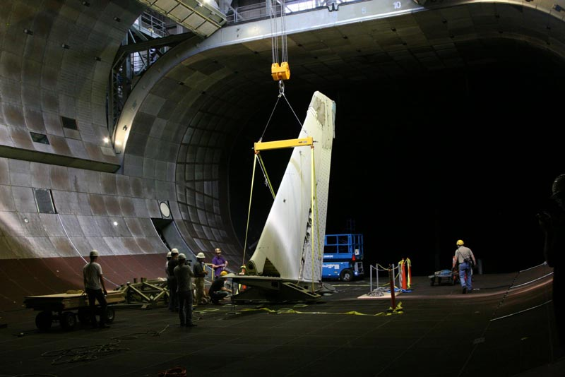 A 40-ton crane carefully lowers an aircraft tail from the rafters down through the open doors of the wind tunnel's roof. Credits - NASA / Eric James.