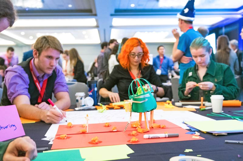 Attendees develop models of innovative solutions using construction paper and tape.