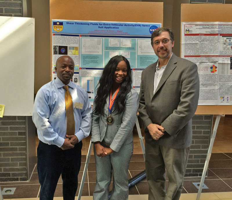 Jehnae (center) poses with Dr. Dean Swinton (left) and Dr. Norman Wagner (right) in front of a poster documenting her work on the NASA project. Photo courtesy of Jehnae Linkins.