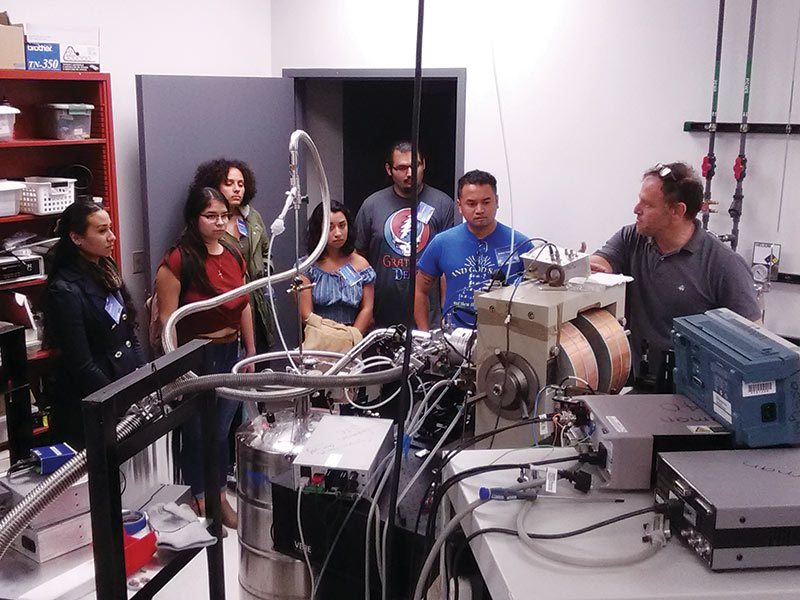 Cal-Bridge scholars tour a physics lab during orientation at the University of California, Santa Cruz.
