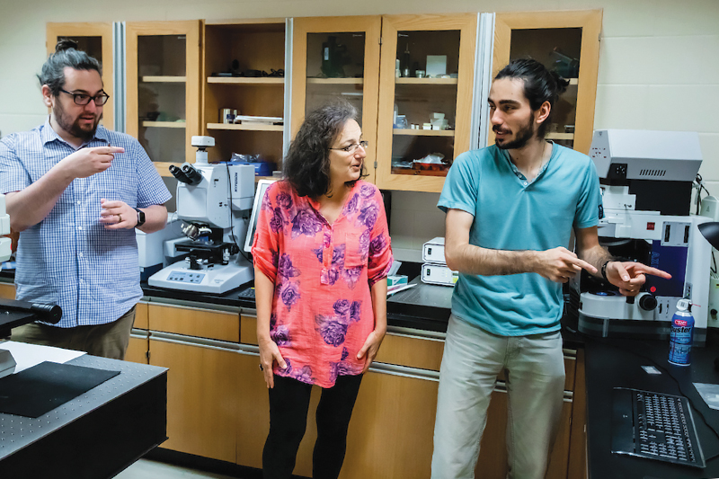 Physics professor Mariana Sendova (center), SPS president Matt Mancini (left), and treasurer Alex Sturzu (right) work together on the CRAIC microspectrophotometer and discuss the analysis needed on newly received glass samples. Photos courtesy of New College of Florida.