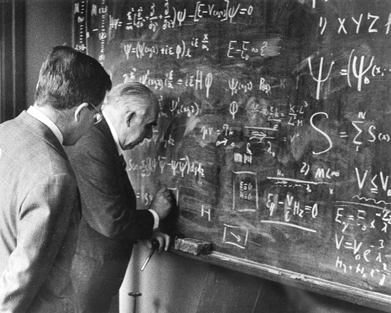 Niels Bohr (right) and son Aage Bohr (left) stand at a blackboard writing equations. Image courtesy of the AIP Emilio Segrè Visual Archives, Margrethe Bohr Collection