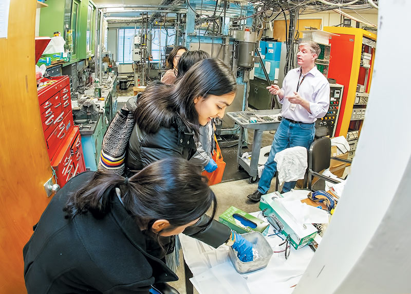 Camila López Pérez (center) and Shanjida Khan (foreground) observe Galinstan, a compound made of gallium, indium, and tin, during the Princeton Plasma Physics Laboratory tour. Photo courtesy of Elle Starkman.
