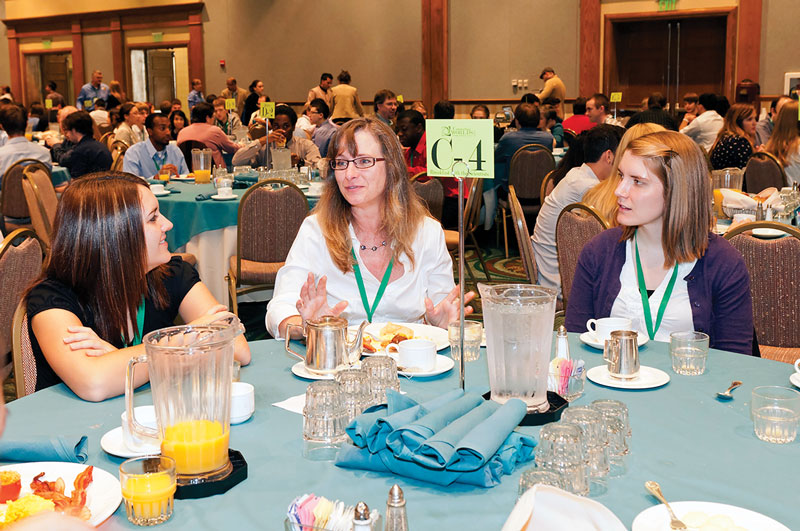 """Connecting Academia and Industry"" workshop leader Shelly Arnold (center) engages with students at the Breakfast with the Scientist event."