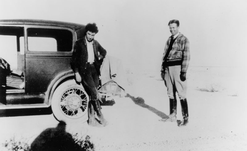 "Robert Oppenheimer (left) and Ernest Lawrence  at Oppenheimer's New Mexico ranch, Perro Caliente (""hot dog""). The car may be a 1930 Chrysler 77 Crown Coupe. Photo courtesy of the AIP Emilio Segrè Visual Archives."