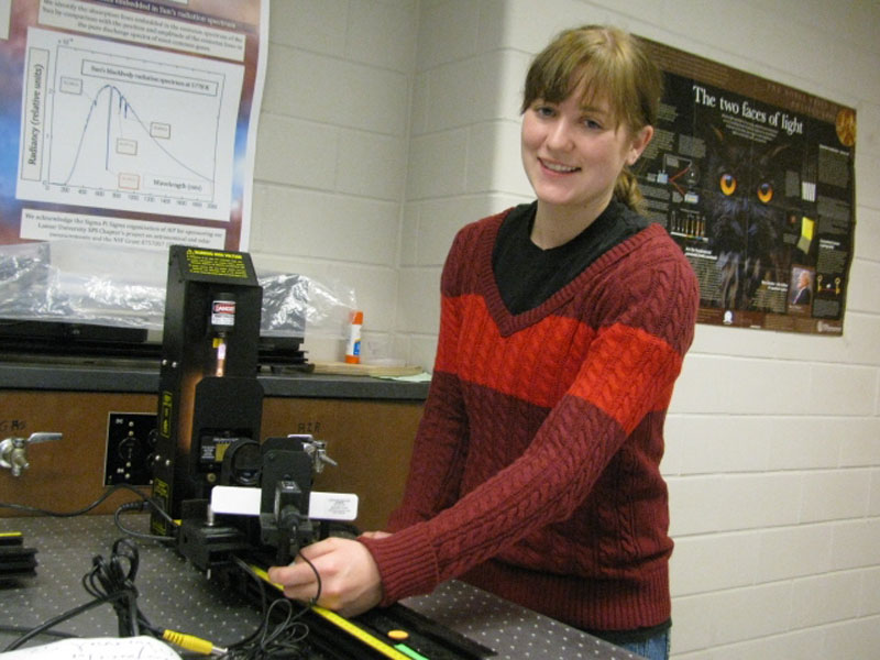 The author poses with the atomic spectroscopy setup in  Lamar University's optics lab.