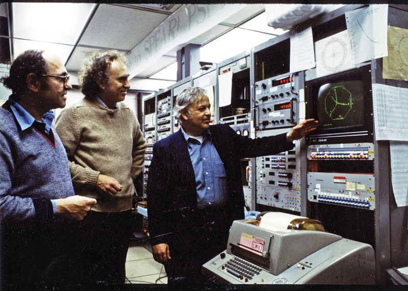 November Revolution publicity photo of Burton Richter, Martin Perl, and Gerson Goldhaber, standing in front of SLAC experimental equipment, 1974. Photo courtesy of SLAC National Accelerator Laboratory.