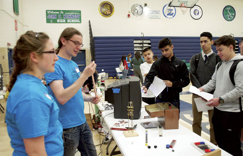Allison Tucker and Nick Smith explain Lenz's law and the ideas of eddy currents to a group of students. Photo by Fran Mallett.