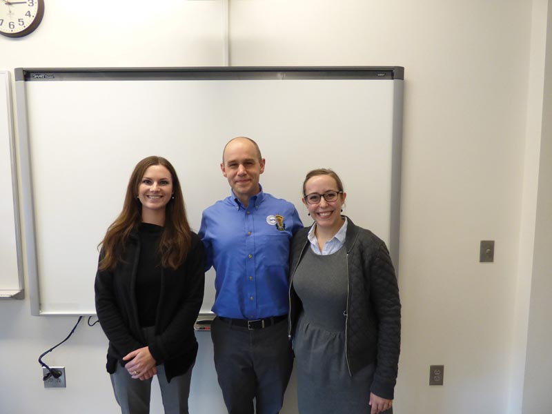 Wren Gregory (L) and Ashlyn Rickard (R) told students what graduate school is really like during their workshop, and posed here with SPS Director Brad Conrad. Photo by Michael Ruiz, UNC Asheville.