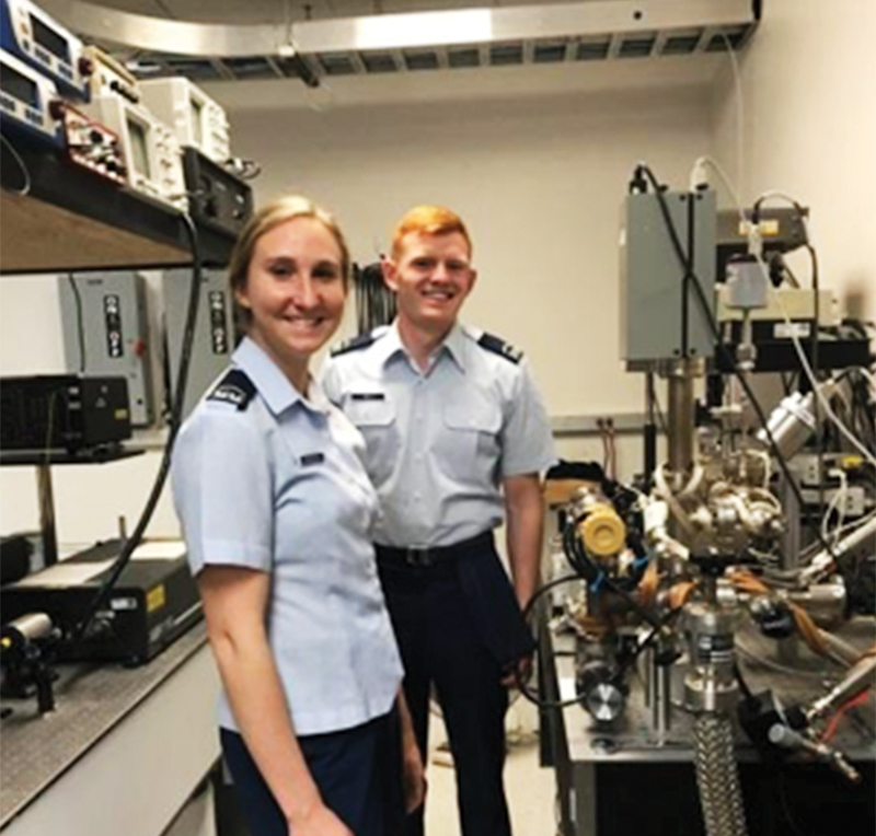 Cadets Lucy Zimmerman and Philip Rich posing in front of the vacuum system while adjusting the buffer gas pressure in preparation for collecting the fluorescence photons. All photos courtesy of Dr. Alina Gearba-Sell.