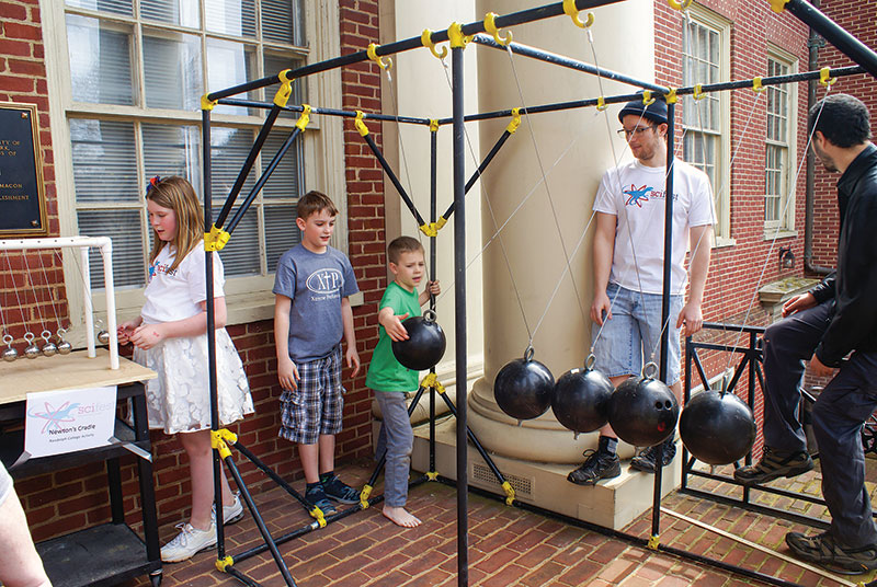 Attendees enjoy the Newton's cradle, a past SPS project, during  SciFest Sunday.