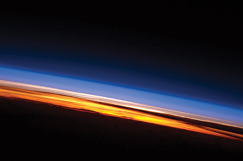 Sunset on the Indian Ocean as seen by astronauts aboard the International Space Station. The image presents an edge-on, or limb view, of Earth's atmosphere as seen from orbit. Earth's curvature is visible along the horizon line, or limb, that extends across the image from center left to lower right. Above the darkened surface of Earth, a brilliant sequence of colors roughly denotes several layers of the atmosphere.