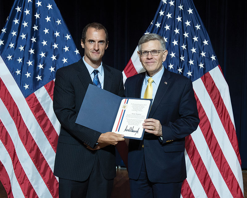 Heimbeck (left) receives the Presidential Early Career Award for Scientists and Engineers (PECASE) from Kelvin Droegemeier, Director of the United States Office of Science and Technology Policy, during a ceremony in July 2019.