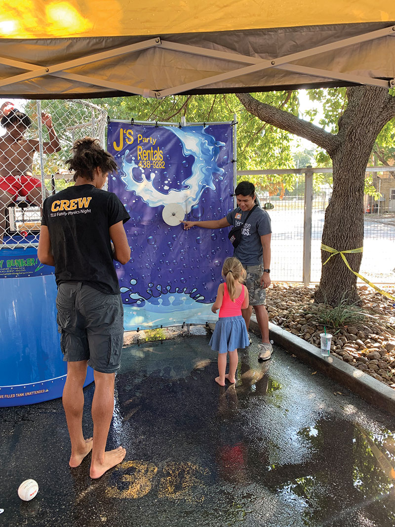A Texas Lutheran SPS volunteer explains the dunk tank rules to an attendee. Photos courtesy of the SPS chapter of Texas Lutheran University.