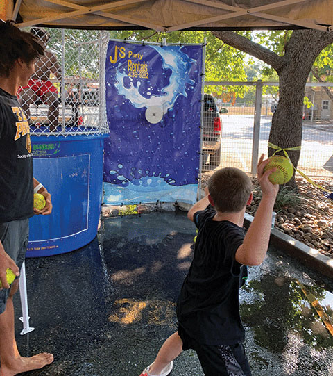 An attendee gets ready to send the dunk tank volunteer for a swim.