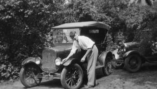 Hendrik Casimir washing a Ford Model T in Ann Arbor, Michigan. The T model was built 1908–1927. This would not be an early T, which had brass radiators. See more photos of physicists and their cars on page 32. Photo by Samuel Goudsmit, courtesy of the AIP Emilio Segrè Visual Archives, Goudsmit Collection.