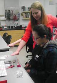 Luisa (front) shows the working proximity sensor circuit and program she created.