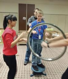 Kathleen Miller-Chell and Tye Williams coach a young man in how to use the spinning wheel on the platform to experience angular momentum.