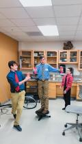Middle schoolers try out a rotating platform demonstrating the conservation of angular momentum.