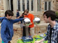 """Rhodes College SPS members with the Van de Graaf generator at the annual """"Rites to Play"""" carnival."""